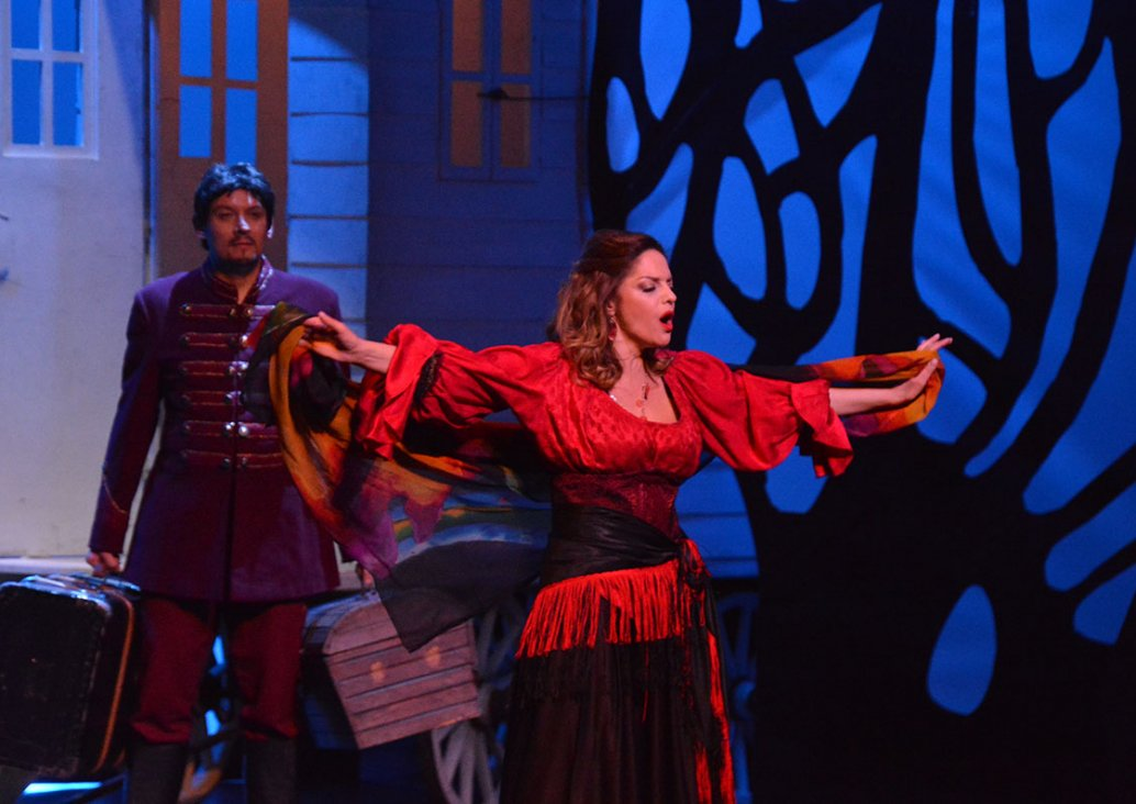 A duet scene, in the foreground a soloist in a gypsy costume - a black skirt and a red blouse with buffy sleeves ending in a frill, tied with a black scarf with red tassels. In her arms extended along her shoulders, she holds a colorful scarf. Behind her