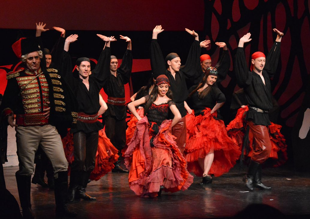 A group scene, on the left side the soloist dressed in officer boots, light pants, short, black and red two row military jacket with golden buttons and red pagons with golden fringes. He has a chako on his head. The rest of the stage is taken up by dancer