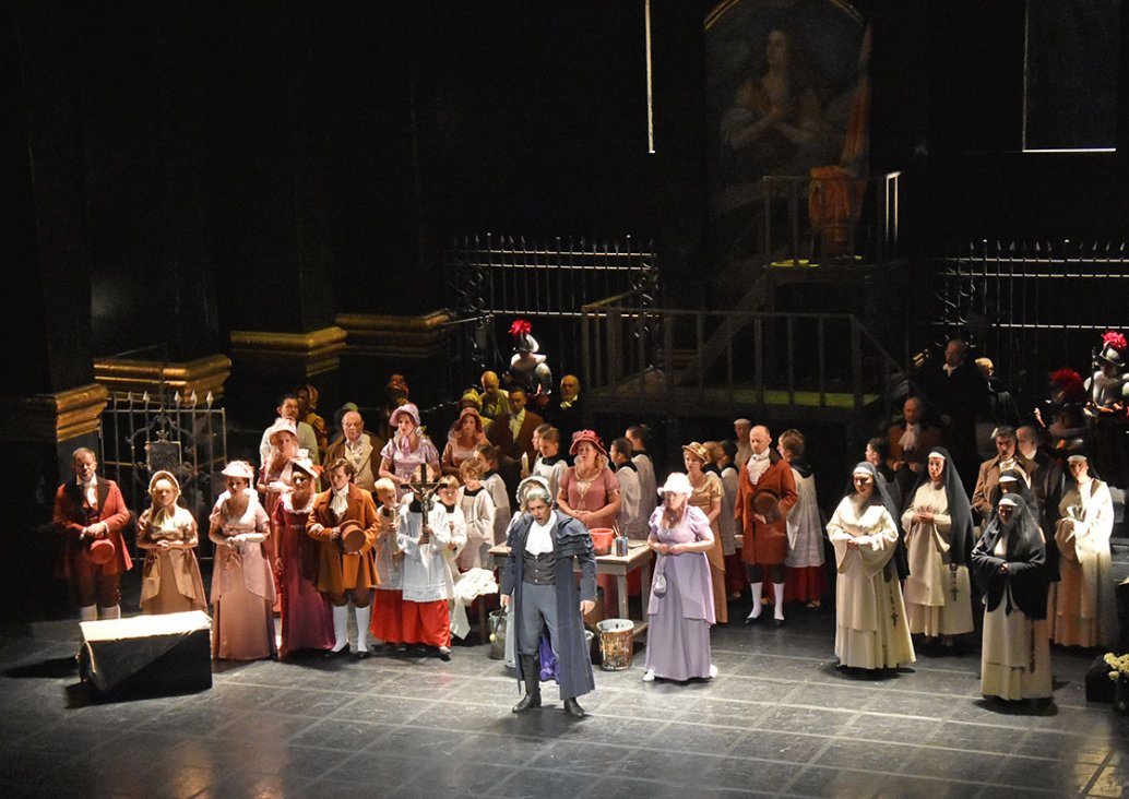The group stage, in the middle, a soloist in grey bourgeois costume, on the sides and behind him characters in colourful bourgeois costumes, altar boys, nuns and guards. One of the altar boys is holding a cross. Behind the soloist, there is a table with p